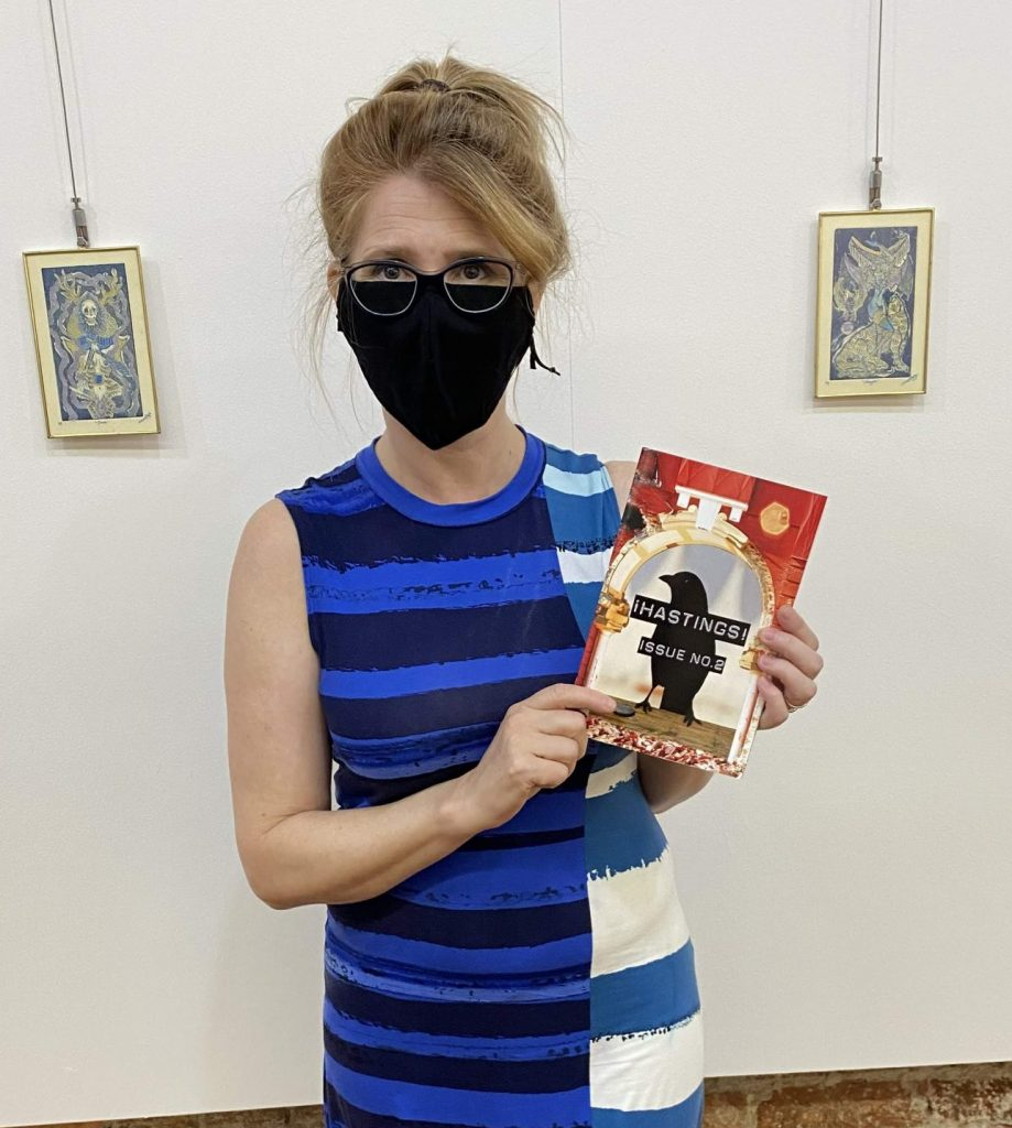 J.G. Chayko in a long blue dress, masked, holding her contributor's copy of a new literary magazine.